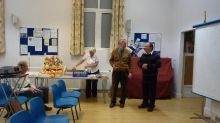 Roy on the right with Chairman Liam Hutchings and Roy's wife Trish on the produce stall at the back